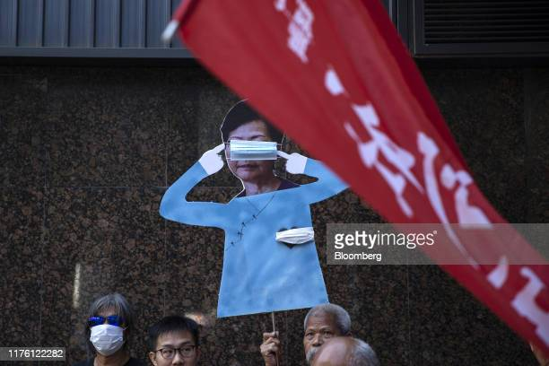 Activist Leung Long Hair Kwokhung left and other demonstrators display a cutout of Hong Kong Chief Executive Carrie Lam with a mask covering her eyes...