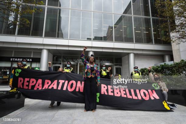 Activist Marvina Newton makes a raised fist gesture outside the headquarters of BlackRock investment company during Extinction Rebellion march...