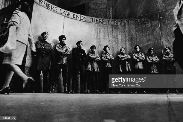 Activist members of the Black Panthers stand in a line with their arms folded during a demonstration outside the city courthouse, New York City,...