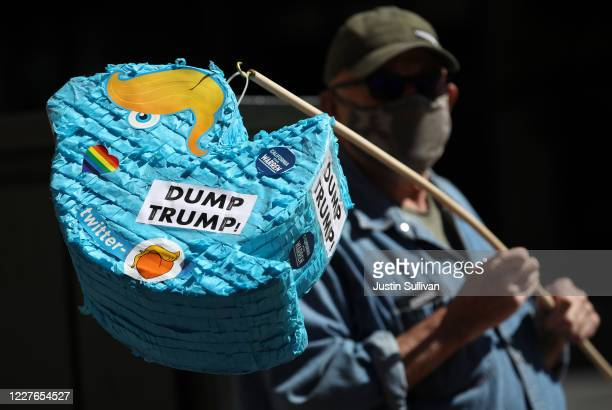 Activist Mike Merrigan holds a piñata shaped like the Twitter logo with hair to look like U.S. President Donald Trump during a protest outside of...