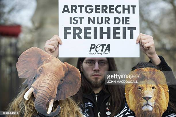 Activist of the animal rights organization PETA wear masks and hold a placard that reads Only liberty is speciesappropriate in front of Berlin's zoo...