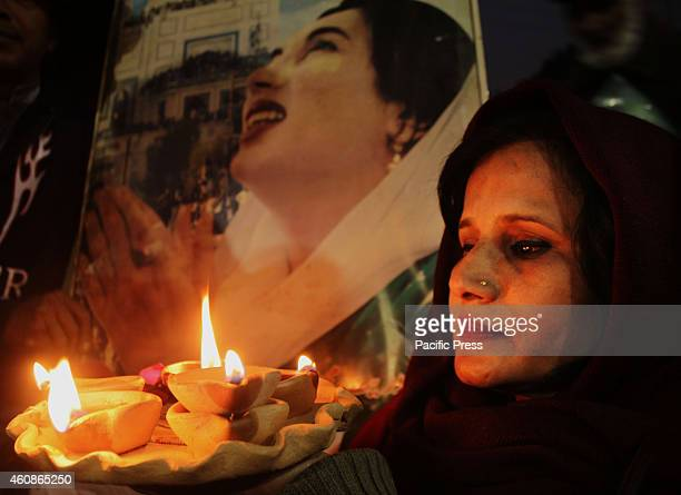 Activist of the Pakistan Peoples Party Human Right wing lits candles on the eve of 7th death anniversary of former Prime Minister Benazir Bhutto at...
