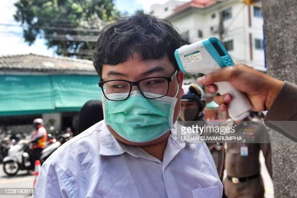 "Activist Parit ""Penguin"" Chirawak gets his temperature taken as a precautionary measure against the spread of the COVID-19 novel coronavirus as he..."