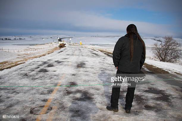 Activist Pete Sands of the Navajo Nation stands at a rope and looks out over an area set as a border line where the police guard a bridge near Oceti...