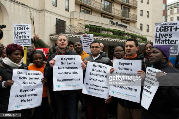 Activist Peter Tatchell and other protesters are seen holding placards outside the Dorchester Hotel during the protest condemning the new antiLGBTIQ...