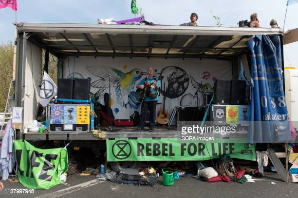 A activist play music in a lorry on Waterloo Bridge that is used as stage for speakers and music events during the Extinction Rebellion Strike in...