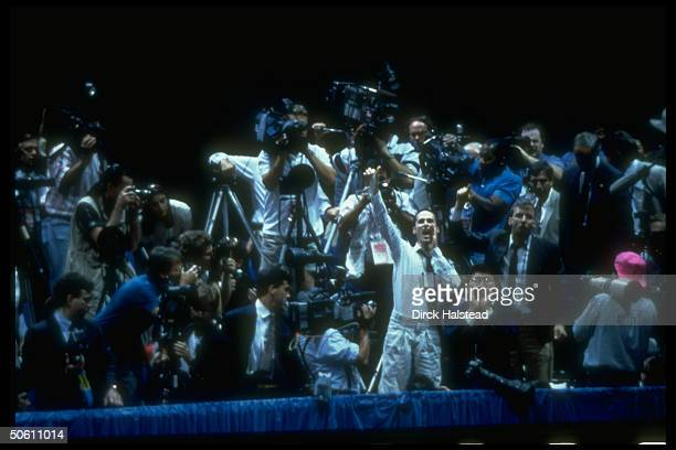 AIDS activist surrounded by reporters cameramen in press box waving unrolled condom heckling Pres Bush during Repub Natl Convention rally in Astrodome