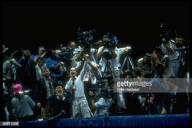 Activist, surrounded by reporters & cameramen in press box, waving unrolled condom, heckling Pres. Bush during Repub. Natl. Convention rally in...