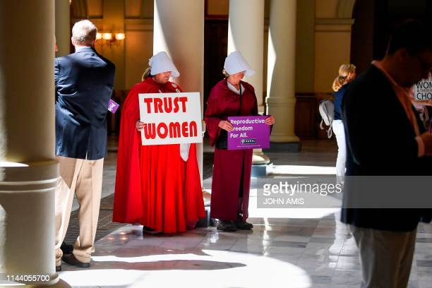 Activist Tamara Stevens with the Handmaids Coalition of Georgia holds a sign as Democratic presidential candidate Sen. Kirsten Gillibrand addresses...