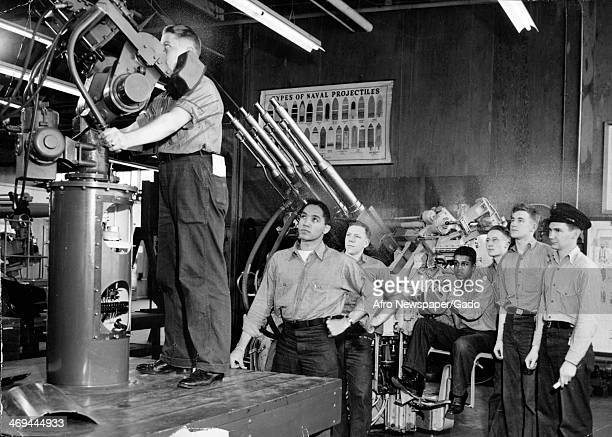 Activist Walter White leader of the NAACP observes United States Navy troops training to use a large bore gun May 6 1945