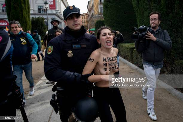 A FEMEN activist with body paint reading 'To fascism neither honor nor glory' is detained by police during a rally commemorating the 44th anniversary...