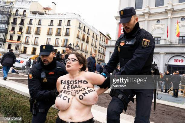 This image contains nudity A FEMEN activist with body painting reading 'Fascism is legal National shame' is escorted away by a police officer during...