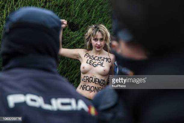 This image contains nudity A FEMEN activist with body painting reading 'Fascism is legal National shame' protests as police officers restrain her...