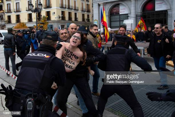 A FEMEN activist with body painting reading 'Fascism is legal National shame' protests as police officers restrain her while Falange's movement...