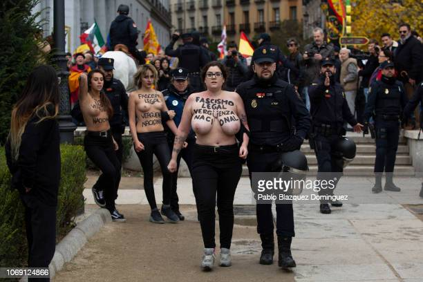 A FEMEN activist with body painting reading 'Fascism is legal National shame' is escorted away by a police officer during a rally commemorating the...