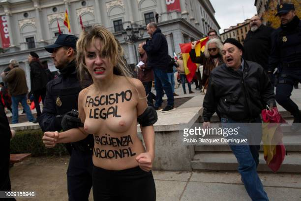 A FEMEN activist with body painting reading 'Fascism is legal National shame' protests as police officers restrain her during a rally commemorating...