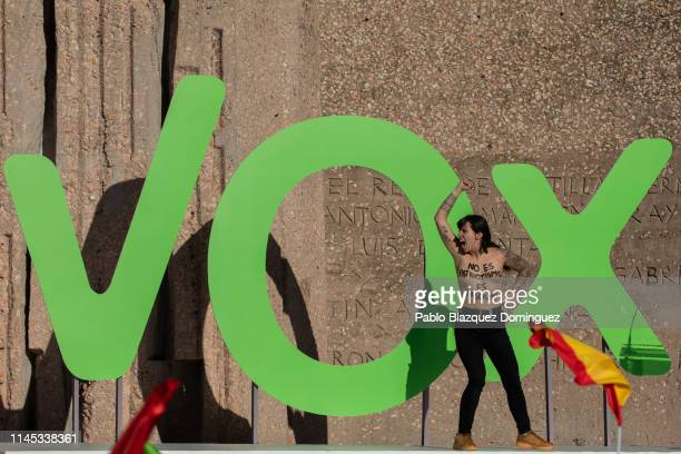 A FEMEN activist with body painting reading 'It is not patriotism it is fascism' protests on stage during the VOX closing rally on April 26 2019 in...