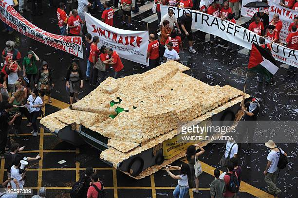 Activists accompany a float representing a tank covered with bread during the Global March along Rio Branco avenue during the People's Summit in Rio...