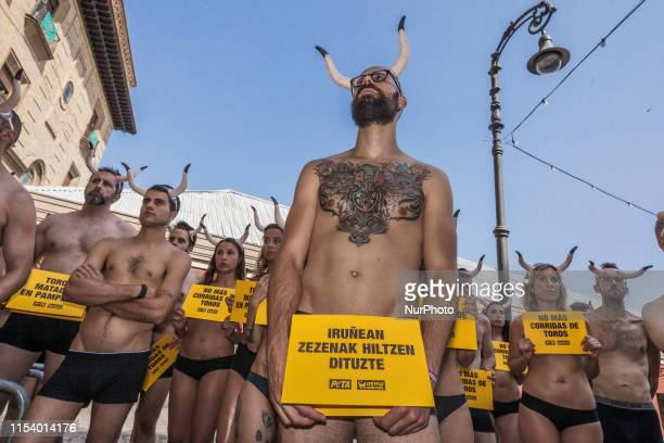 Activists against animal cruelty hold banners anti bullfightings in many languages and horns in head during a protesting performance before the San...