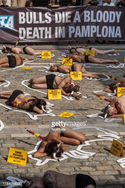 Activists against animal cruelty in bullfightings lie on the ground like dead bodies inside chalk outlines of bulls during a protest performance...