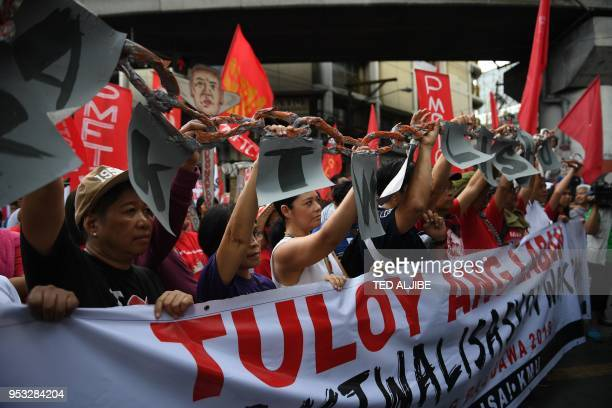 Activists along with workers hold a mock chain as they march towards Malacanang Palace during the May Day rally in Manila on May 1 2018