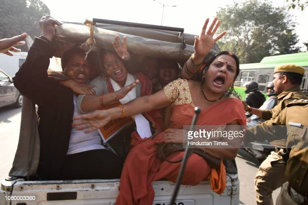 Activists and members of various Hindu groups shout slogans to demand the construction of the Ram Temple as they are detained, near the Supreme Court...