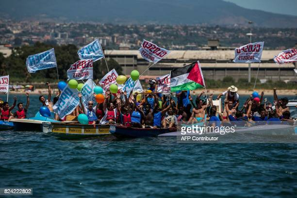 Activists and migrants on canoes hold balloons and flags as they take part in an antiracism protest off a beach near the port of Catania in Italy on...