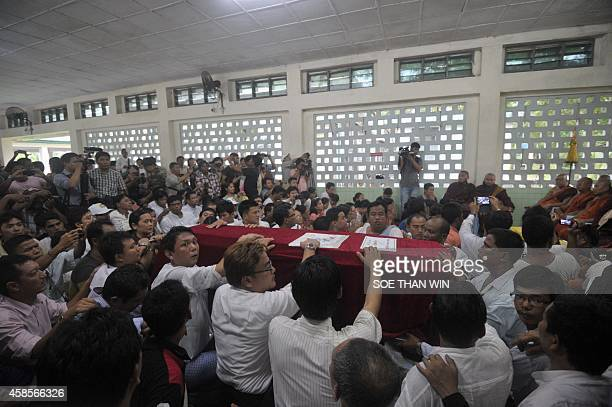 Activists and relatives gather around the coffin of Aung Naing during a funeral following his exhumation and autopsy in Yangon on November 7 2014 The...