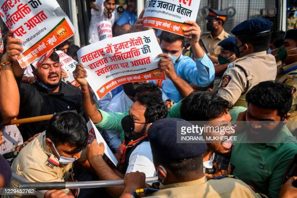 Activists and supporters of Bharatiya Janata Party hold placards as they scuffle with police while protesting against the arrest of Indian television...
