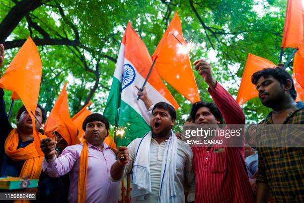 Activists and supporters of Hindu Sena a right wing group celebrate after Indian president signed a decree abolishing Article 370 of the constitution...