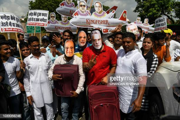Activists and supporters of the Indian Youth Congress wear masks bearing images of Finance Minister Arun Jaitley businessman Vijay Mallya and Prime...