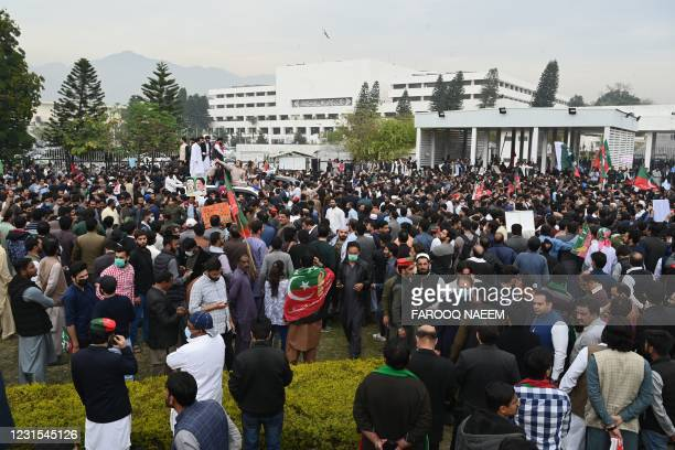 Activists and supporters of the ruling Pakistan Tehreek Insaf party shout slogans as they gather outside the National Assembly during a vote of...