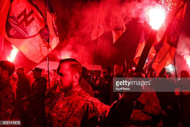 Activists and supporters of Ukrainian nationalists hold a torch and flags, as they march in downtown Kiev during a rally. The march was confined to...