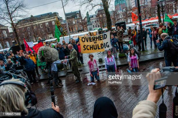 XR activists are doing a performance in front of the Tweede Kamer during a demonstration in support of the Urgenda case that took place in front of...