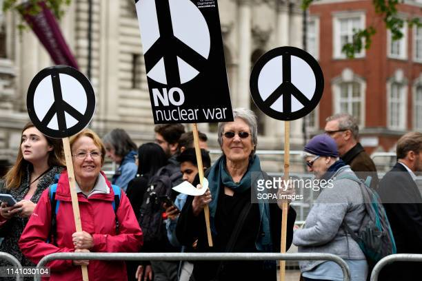 Activists are seen holding placards during the protest Antinuclear activists gathered opposite Westminster Abbey in London to protest against a...