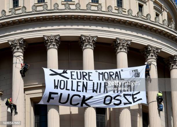 Activists attach a banner reading 'we don't want your morals fuck OSCE' onto St Nicolas Church in Potsdam Germany 22 August 2016 They protest against...