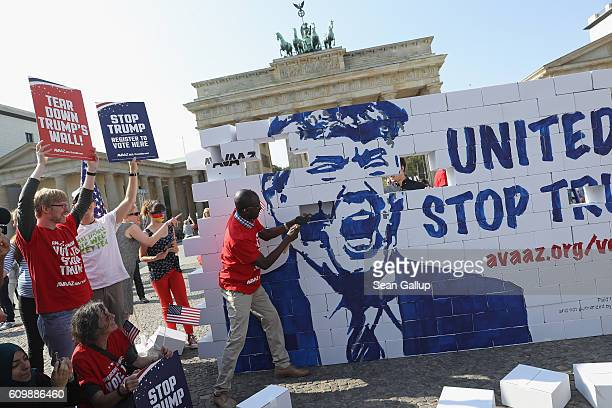 Activists bash down what they called a cardboard 'Wall of Hate' showing Republican US elections candidate Donald Trump in front of the Brandenburg...