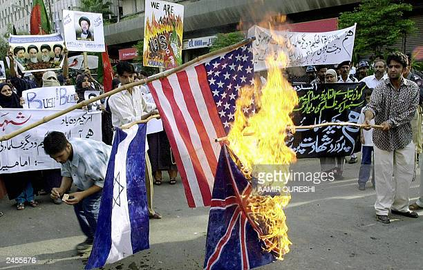 Activists belonging to the Pakistani Shiite Muslim group the Imamia Student Organisation set fire to British US and Israeli flags as other activists...