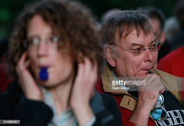 Activists blow whistles during a demonstration in the Schlosspark next to Hauptbahnhof train station on October 6 2010 in Stuttgart Germany...