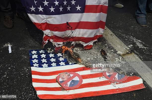 Activists burn a mock US flag with Presidentelect Donald Trump's portrait and a real one during a rally in front of the US embassy in Manila on...