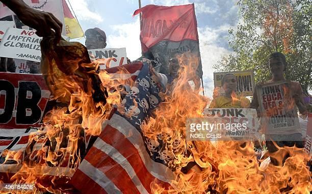 Activists burn a US flag during an anti Asia-Pacific Economic Cooperation protest in front of the US embassy in Manila on November 12, 2015. The...