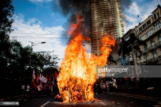 Activists burn an effigy of Philippine President Rodrigo Duterte near the US Embassy in Manila on November 30 during the commemoration of the 155th...