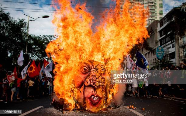 TOPSHOT Activists burn an effigy of Philippine President Rodrigo Duterte near the US Embassy in Manila on November 30 during the commemoration of the...