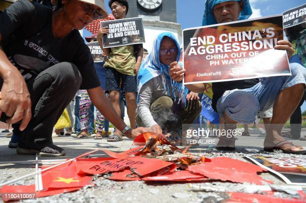 Activists burn Chinese flags and display antiChina placards during a protest at a park in Manila on June 18 after a Chinese vessel last week collided...