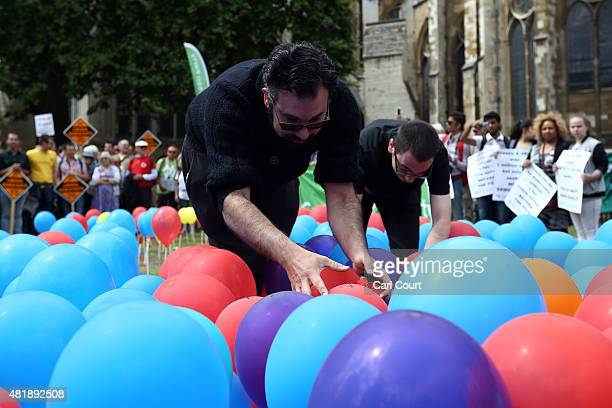 Activists burst balloons depicting the United Kingdom to highlight the perceived lack of fairness in the voting system during a Youth Parliament...