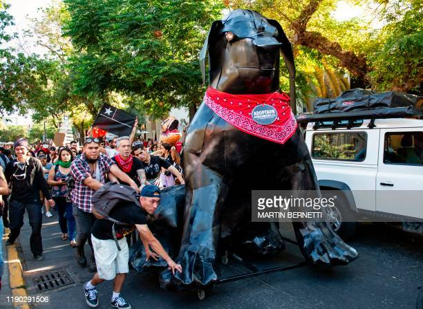 TOPSHOT Activists carry a metal sculpture of the socalled Negro Matapacos dog in Santiago on December 20 2019 The social movement that broke out in...