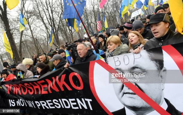 Activists carry a placard depicting Ukrainian President Petro Poroshenko and reading 'Poroshenko is not my president' during a mass rally calling for...