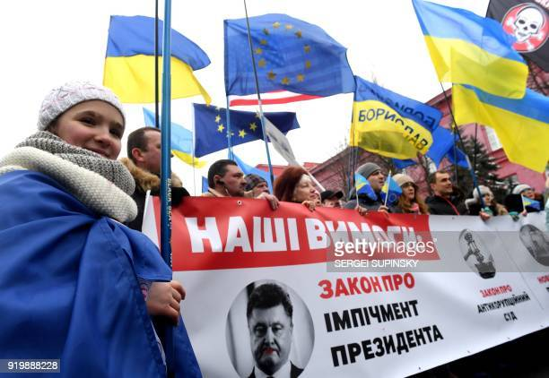 Activists carry a placard depicting Ukrainian President Petro Poroshenko and reading 'Our requirements impeachment law' during a mass rally calling...