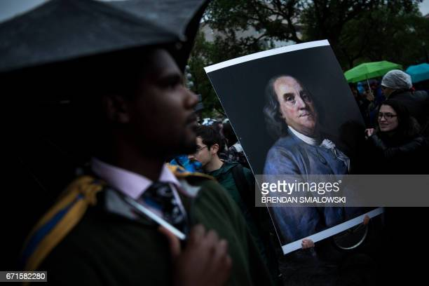 Activists carry a portrait of Benjamin Franklin during a march for science April 22 2017 in Washington DC Thousands of people joined a global March...