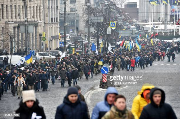 Activists carry flags and shout slogans during a mass march and rally calling for the impeachment of Ukrainian president Petro Poroshenko organized...